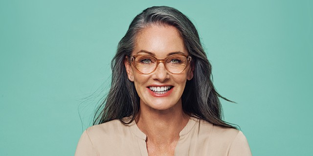 A happy woman wearing designer glasses