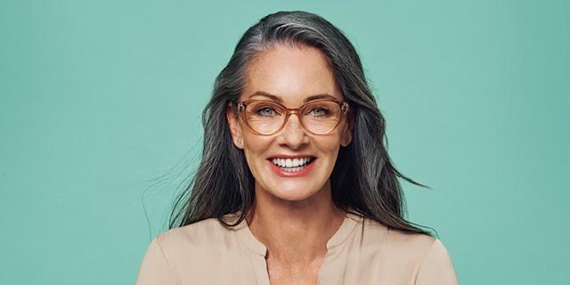 A happy woman wearing designer glasses
